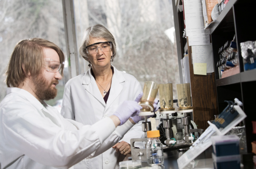 Professor Diana Downs interacts with graduate student Andrew Borchert inside a biology laboratory.